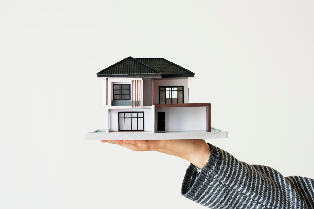 hand presenting model house home loan campaign